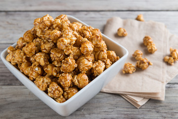 Caramel popcorn on wooden background