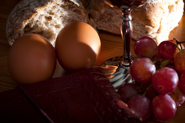 Holy Communion and Easter concept with The Holy Bible. Bread, eggs, grapes and a silver chalice of red wine