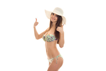 a young girl in a bathing suit and hat worth turning sideways and shows the class