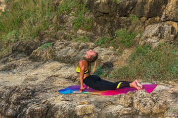 Woman stretching in mountains. Young woman stretching while doing yoga. Horizontal outdoors shot.