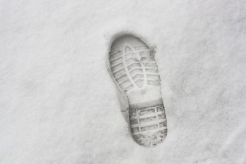 Hard shoe footprint on white snow surface in winter