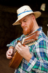 Hipster man with red beard playing the guitar
