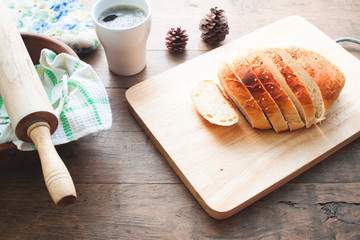 loaf of bread on wood background with cup of coffee and bakery tools, food closeup