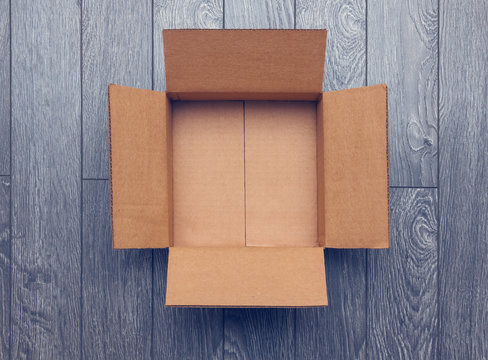 Flat lay of empty open box on wooden surface