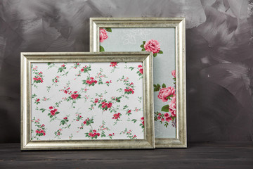 Two vintage photo frames with texture roses on shabby gray background.