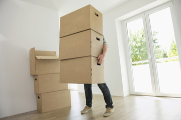 Man carrying heavy boxes moving in new home