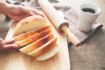 Woman hand holding loaf of bread on wooden plate with kitchen tools and cup of coffee