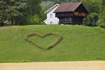 Norwegian traditional farm house and heart symbol in the countryside.