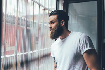 Young bearded man overlooking leaning window