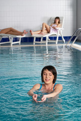Young attractive woman relaxes in pool in fitness center