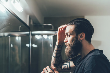 Young man combing hair while looking in mirror
