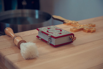 Bible and orthodox cross during blessing. Shallow depth of field.