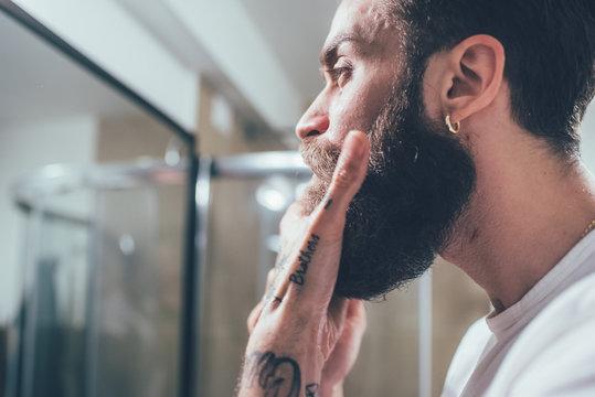 Young man indoor brushing his beard