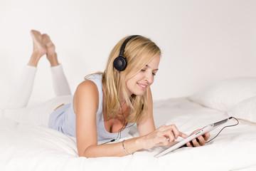 Junge Frau liegt mit Tablet und Kopfhörer auf einem Bett