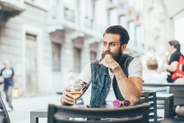 Young bearded tattooed man overlooking serious