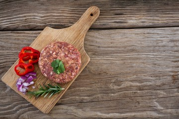 Beef patty and ingredients on wooden tray