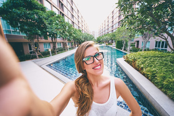 Youth and technology. Pretty young woman taking selfie on swimming pool background.