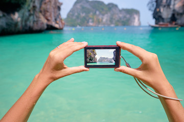 Tourism and vacation. Close up of female hands holding camera, taking picture of beautiful tropical seascape.