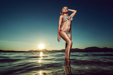 summer fashion photography with pretty woman staying in water, glamour photography with bikini