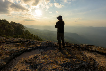 Man on the top of a rock to face the sunset - success concept