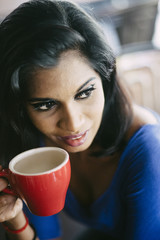 Close-up of young woman holding coffee cup in a cafe
