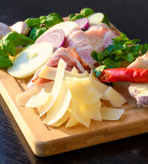 Raw smoked bacon slices on wooden board with onion, garlic, cheese and herbs