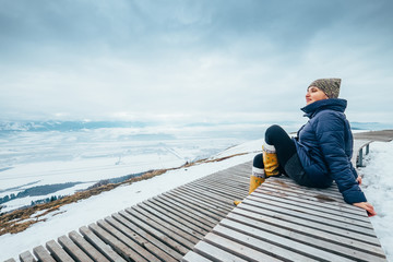 Woman enjoys with beautiful top view on winter landscape