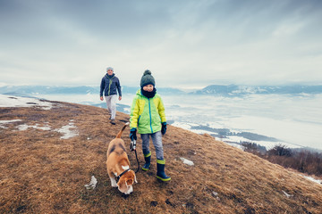 Son and father walk with dog on hill with top view panorame on city