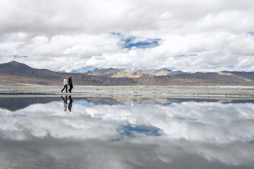 Two travelers walks near Tso Kar Lake in Himalaya Mountain