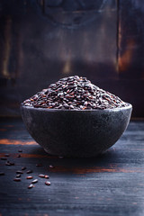 Black rice on black wooden table . Selective focus.