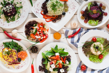 Assortment of fresh vegetable salads flat lay. Top view on vegetarian buffet with tasty side dish variety. Healthy food set, organic, natural eating concept