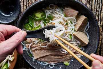 eating vietnamese pho with chopsticks and spoon overhead composition