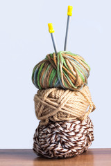 Close Up Of Three Threads For Knitting Green, Brown Colors And Spokes On Wooden Board On White Background.