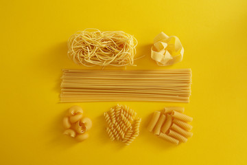 Assorted types of pasta on yellow background.
