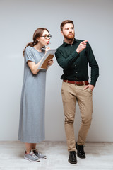 Female nerd and bearded man look toward