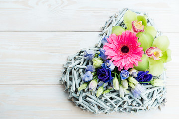 heart gift of fresh flowers on a wooden background
