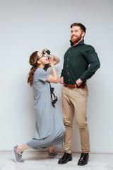 Vertical image of Female nerd making photo of bearded man