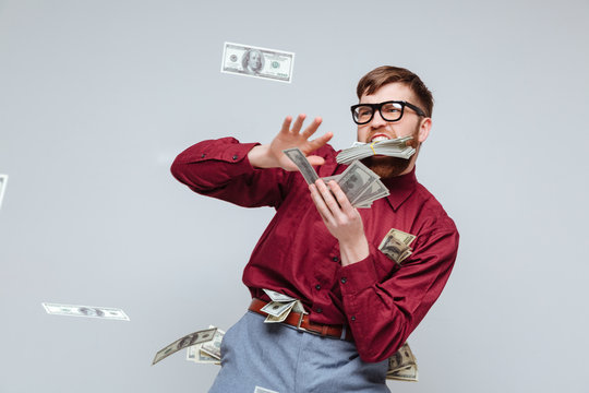 Happy Male nerd playing with money