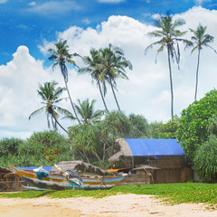 old fishing boats and huts on sandy beach