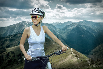 Beautiful woman in helmet and glasses stay on the bicycle around
