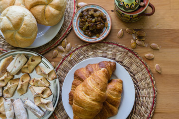 Croissant, buns and homemade cookies on wooden table background
