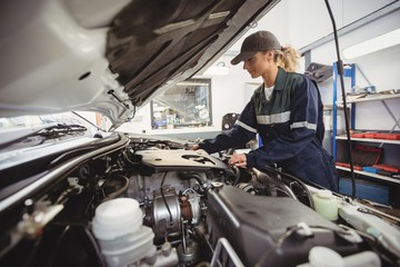 Female mechanic servicing car