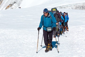 Mature Guide leading Group of Mountain Climbers on Glacier