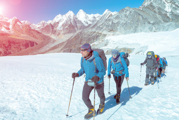 Mountain Climbers walking up on Glacier in weather protective Clothing