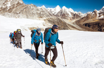 Group of Climbers walking on Glacier in high Mountains