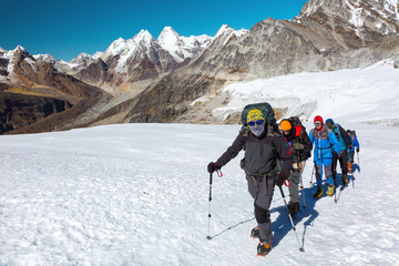 Severe Mountain Climbers in weather protective Clothing on Glacier