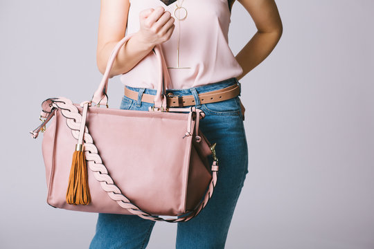 Fashionable young woman in casual clothes holding pink clutch isolated on gray background