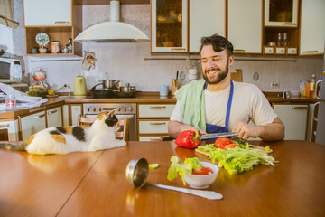 a man cooks in the kitchen beside him sits a funny beautiful cat