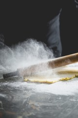Flour on a work surface with a rolling pin and shortcrust pastry
