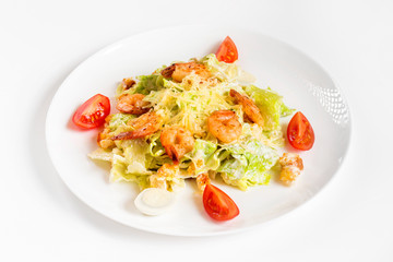 Plate of caesar salad with shrimps isolated at white background.